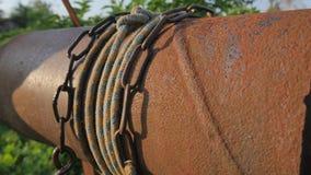 La donna cade la catena con il secchio nel pozzo rustico per estrarre l'acqua Fine d'annata della catena del pozzo d'acqua su Vec archivi video