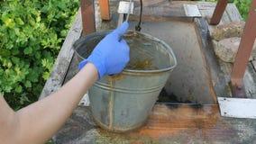 La donna cade la catena con il secchio nel pozzo rustico per estrarre l'acqua La ragazza versa l'acqua nel secchio stock footage