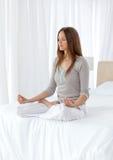 La donna calma che fa l'yoga si esercita sulla base Fotografie Stock