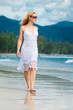 La donna cammina su una spiaggia Fotografia Stock