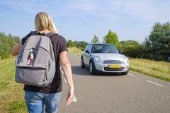 La donna cammina sulla strada con traffico imminente Fotografia Stock Libera da Diritti