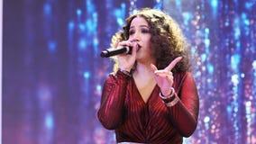 La donna canta la canzone felice contro lo schermo digitale archivi video