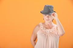 La donna capovolge il suo cappello Immagini Stock