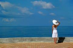 La donna in cappello bianco esamina il mare Fotografia Stock