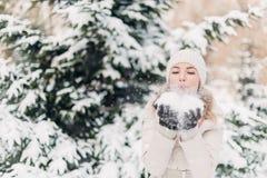 La donna in cappello dell'inverno scarica la neve dalle mani Fotografia Stock