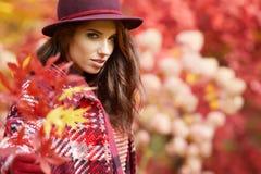 La donna in cappotto con il cappello e la sciarpa in autunno parcheggiano Fotografie Stock