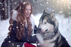La donna in cappotto grigio con un cane o un lupo immagine stock