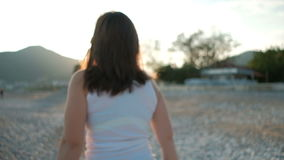 La donna castana è felice di osservare la luce solare sulla costa del mare nella festa stock footage
