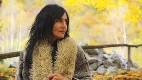 La donna castana abbastanza giovane sembra malinconica nell'atmosfera di autunno video d archivio