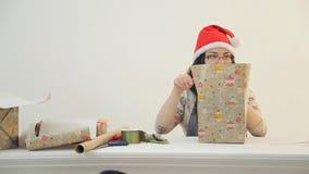La donna castana asiatica si siede la scatola del presente del nuovo anno degli involucri in studio video d archivio