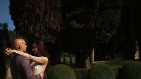 La donna castana attraversa le sue mani sul collo del ` s dell'uomo stock footage