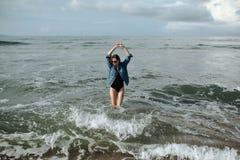La donna castana di sorriso felice che porta il rivestimento nero del denim e del costume da bagno al fondo dell'oceano gode di d fotografia stock libera da diritti