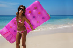 La donna castana esile prende il sole con un materasso di aria immagini stock libere da diritti