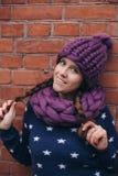 La donna castana nella porpora ha tricottato il cappello e la sciarpa Immagine Stock