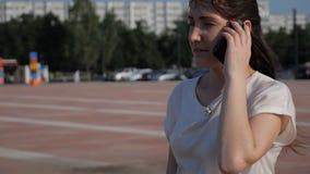 La donna castana nella via sta cadendo un telefono mentre parlava archivi video