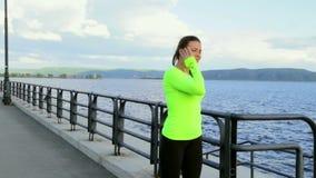 La donna castana in panno di sport che ascolta la musica all'argine prende una rottura video d archivio