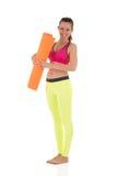 La donna castana sorridente nelle ghette gialle al neon di sport ed in reggiseno rosa che stanno con l'arancia ha rotolato la stu Immagini Stock Libere da Diritti