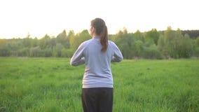 La donna castana sta facendo gli esercizi nel campo all'alba stock footage