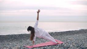 La donna castana sta facendo l'aria aperta di allenamento nella riva del ciottolo del mare stock footage