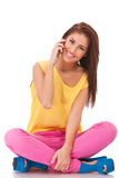La donna casuale è sedentesi e comunicante sul telefono Fotografie Stock Libere da Diritti