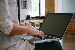 La donna casuale di affari lavora online sul computer portatile che passano su K Fotografia Stock