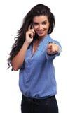 La donna casuale indica voi mentre sul telefono Immagini Stock Libere da Diritti