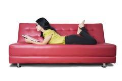 La donna casuale legge un romanzo sul sofà Immagini Stock Libere da Diritti