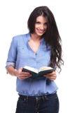 La donna casuale tiene un libro aperto Fotografie Stock Libere da Diritti