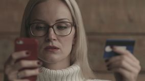 La donna caucasica abbastanza bionda in un pullover bianco fa un acquisto facendo uso di un telefono cellulare e di una carta di  archivi video