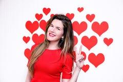 La donna caucasica bianca con le labbra rosse che danno una mano di conteggio (segno due) su un cuore ha modellato il fondo ` S d Fotografia Stock
