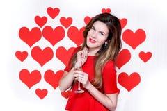 La donna caucasica bianca con le labbra rosse che giudicano un champagne di vetro su cuore ha modellato il fondo ` S del bigliett Immagine Stock Libera da Diritti