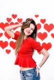 La donna caucasica bianca con le labbra rosse che stanno e che giocano con i capelli su cuore ha modellato il fondo ` S del bigli Immagini Stock Libere da Diritti