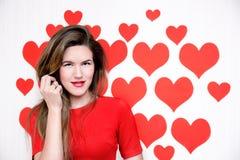 La donna caucasica bianca con le labbra rosse che stanno su un cuore ha modellato il fondo ` S del biglietto di S. Valentino Immagini Stock