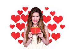 La donna caucasica bianca con le labbra rosse che tengono un cuore del regalo ha modellato il fondo Concetto di giorno di S Fotografie Stock Libere da Diritti