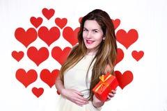 La donna caucasica bianca con le labbra rosse che tengono un regalo in una mano su cuore ha modellato il fondo Concetto di giorno Immagini Stock Libere da Diritti
