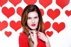 La donna caucasica bianca con le labbra rosse che tengono un rossetto rosso su cuore ha modellato il fondo ` S del biglietto di S Fotografia Stock Libera da Diritti