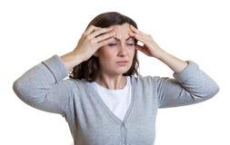 La donna caucasica con capelli scuri ha un'emicrania Fotografia Stock