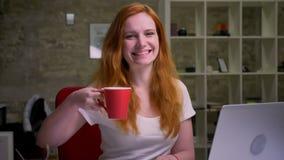 La donna caucasica dai capelli rossi del metraggio sta giudicando la tazza rossa e sorridere, esaminanti felicemente la macchina  stock footage