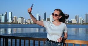 La donna caucasica sta prendendo i selfies dal telefono cellulare, all'aperto nel porticciolo del Dubai nel giorno soleggiato video d archivio