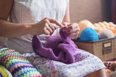 La donna caucasica tricotta i vestiti di lana Ferri da maglia della tenuta alle mani Fotografie Stock
