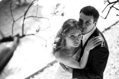 La donna cerca nel cielo attraverso i rami di autunno che abbracciano un uomo Fotografie Stock Libere da Diritti