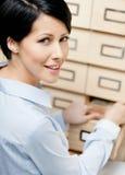 La donna cerca qualcosa nel catalogo di scheda Immagini Stock