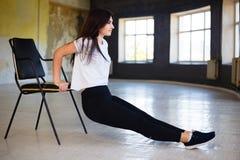 La donna che adatta eseguire inversa spinge aumenta usando la sedia immagini stock