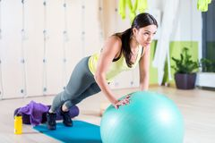 La donna che adatta fare spinge aumenta con il tricipite di addestramento di esercizio di armi di allenamento della palla medica  Fotografia Stock