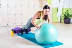 La donna che adatta fare spinge aumenta con palla medica Immagine Stock Libera da Diritti