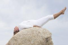 La donna che allunga il corpo esercita all'aperto Immagine Stock