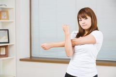 La donna che allunga l'esercizio Immagine Stock
