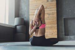 La donna che allunga le mani dietro appoggia alla classe di yoga Immagini Stock Libere da Diritti