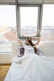 La donna che allunga a letto dopo sveglia nella mattina con luce solare Fotografie Stock Libere da Diritti