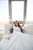 La donna che allunga a letto dopo sveglia nella mattina con luce solare Fotografia Stock Libera da Diritti